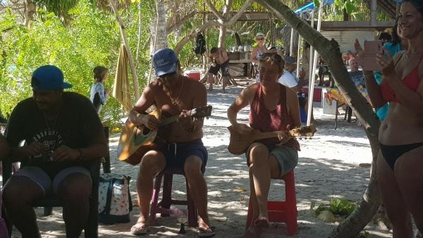 Leslie joue du Ukulele avec des Polynésiens